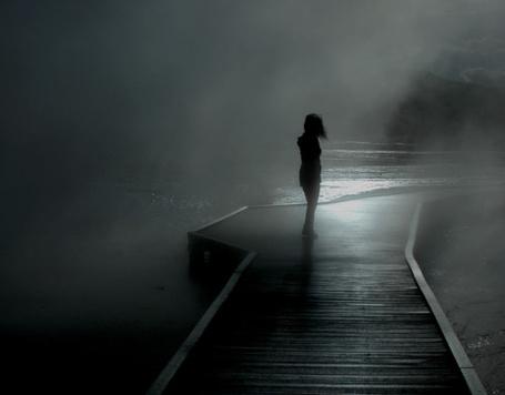 Фото Одинокая девушка стоит на причале ночью в тумане