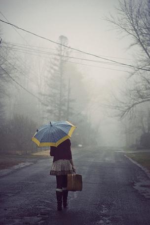 Фото Девушка с зонтом и чемоданом идет по дороге в тумане