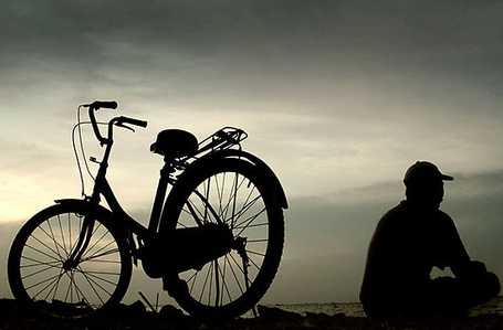 Фото Силуэт мужчины спиной, рядом стоит велосипед на фоне неба