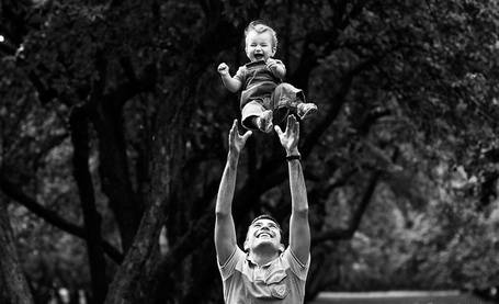 Фото Мужчина, улыбаясь, смотрит на своего малыша, которого подбросил вверх