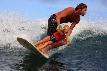 Фото Мужчина с мальчиком катаются по волнам на доске для серфинга