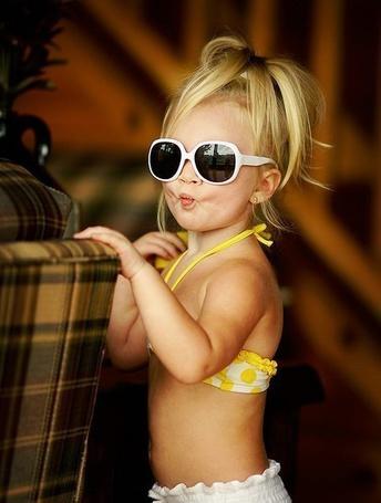 Фото Девочка в очках, купальнике и с хвостиком на голове, кривляет губы