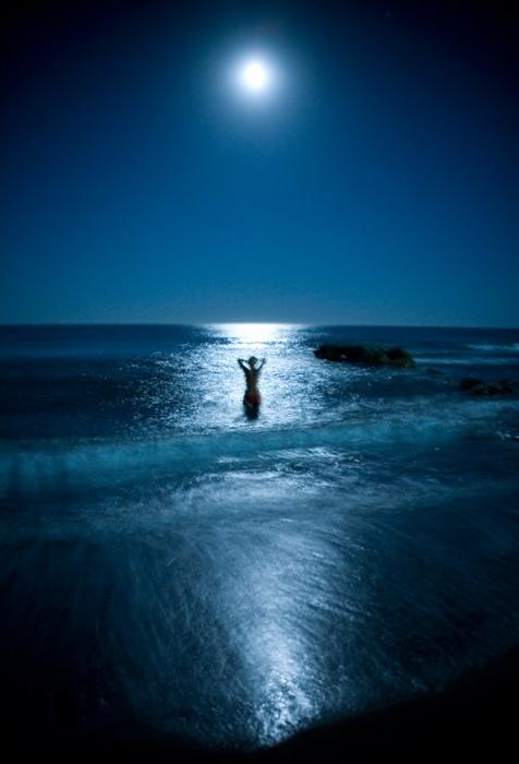Девушка купается в ночном море, в котором отражается луна