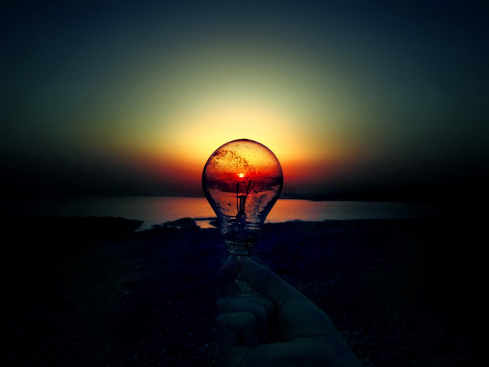 Фото Чья-то рука держит лампочку, через которую видно закат