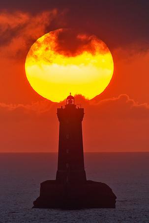 Фото Маяк на фоне заката солнца над морем