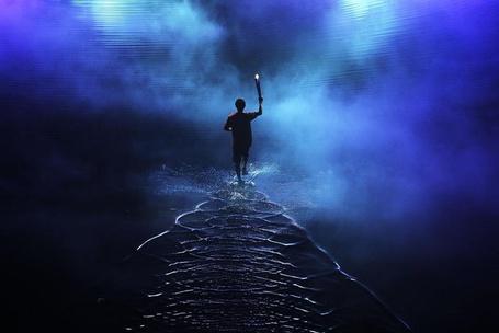 Фото Даррен Чой / Darren Choy из Сингапура / Singapore несет факел Юношеских Олимпийских Игр во время церемонии открытия, фотограф Adam Pretty / Адам Претти
