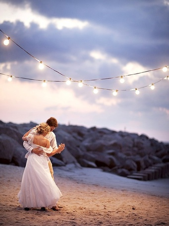 Фото Танцующие жених и невеста на берегу, над натянутыми лампочками на фоне неба