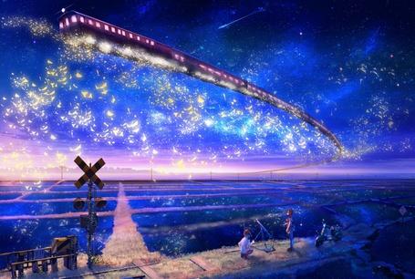 Фото Пара ночью смотрит на летающий в небе поезд