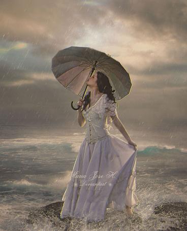 Фото Девушка в длинном платье, с зонтом в руках, стоит на камне у моря, автор MariaJoseHidalgo