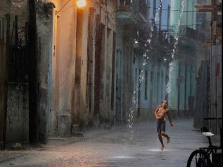 Фото Наслаждаясь дождем мальчик танцует под потоком воды вырывающимся из водосточной трубы, на узкой улочке Старой Гаваны квартала города помнящего Средневековье и входящего в список Всемирного наследия ЮНЕСКО, автор фото Desmo