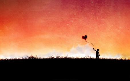 Фото Мальчик стоит с красным воздушным шаром в виде сердца на фоне розового неба