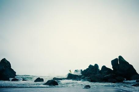 Фото Серфингист стоит на скалах у моря, фотограф Christopher Wilson / Кристофер Уилсон
