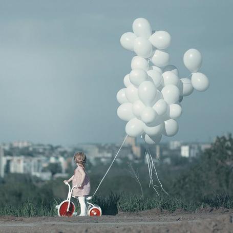 Фото Маленькая девочка стоит на холме, с которого открывается вид на город, рядом с ней велосипед, к которому привязаны белые шарики
