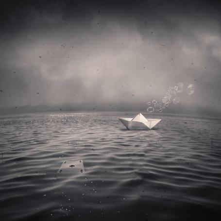 Фото Бумажный кораблик, от которого исходят мыльные пузыри, плавает в море на фоне тумана, фотограф Denis Olivier / Денис Оливер