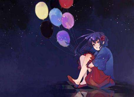 Фото Печальная девушка с цветком в волосах сидит на земле и держит шарики на фоне ночного неба