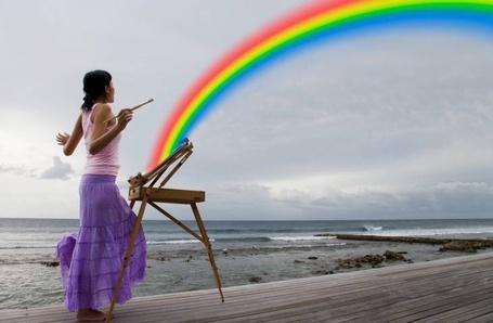 Фото Девушка с кистью в руках стоит на берегу моря и с ее этюдника исходит радуга
