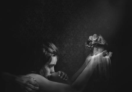 Фото Девушка держит в руках кусочек земли и смотрит на маленькую фею, руки взрослого человека держат ее за плечи