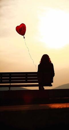 Фото Девушка с красным воздушным шаром в форме сердца, сидит в одиночестве на краю лавочки