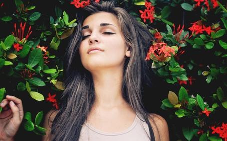 Фото Девушка с закрытыми глазами лежит на цветах