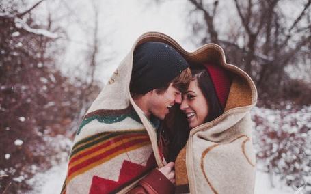 Фото Парень и девушка накрытые одеялом улыбаются друг другу