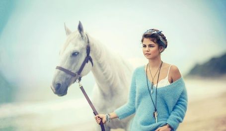 Фото Американская актриса и певица Селена Гомез / Selena Gomez в синем свитере рядом с белой лошадью