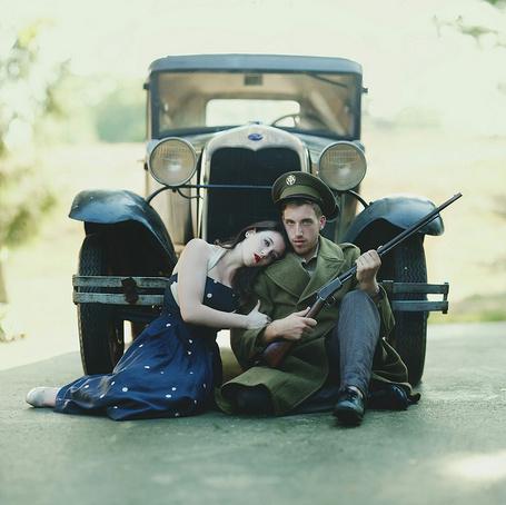 Фото Черноволосая девушка, сидящая на дороге, положила голову на плечо мужчины в военной форме с винтовкой в руках, сидящим рядом и привалившимися к ретро автомобилю