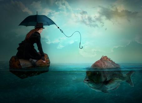Фото Рыжеволосая девушка в черной шляпе, потерпевшая кораблекрушение, плывущая по морю на деревянном сундуке, пытается с помощью веревки с крючком без наживки, привязанной к черному зонтику, поймать крупную рыбу, работа Nataliorion