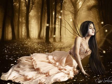 Фото Фея в платье лежит на земле на фоне деревьев