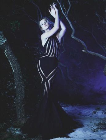 Фото Девушка в элегантном платье, стоящая на снегу возле дерева в ночном лесу