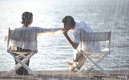 Фото Влюбленные парень и девушка, сидящие на берегу моря на раскладных креслах под сильным дождем; парень целует девушке руку