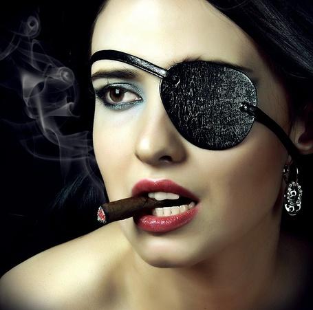 Фото Девушка с повязкой на одном глазу, с сигарой во рту