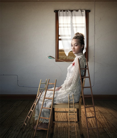 Фото Девушка сидит в пустой комнате на стуле, обставленная небольшими деревянными лестницами, из груди у нее торчит стрела