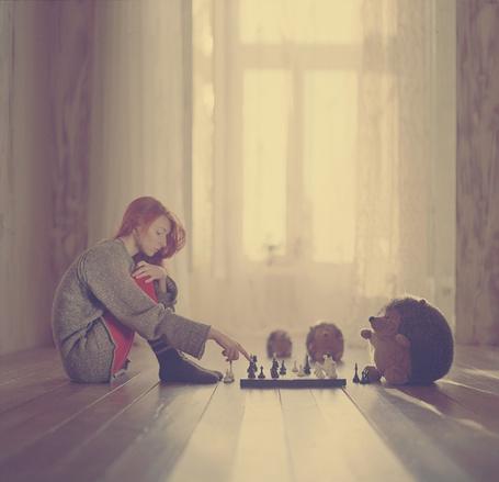 Фото Девушка в пустой комнате сидит на полу и играет с игрушечными ежами в шахматы