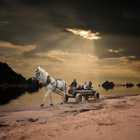 Фото Женщина сидящая на телеге, держащая в руках вожжи, управляет белой лошадью, проезжающей по песчаному берегу реки на фоне пасмурного неба; за спиной возницы в телеге также сидят три женщины и ребенок, фотография Garas Lonut