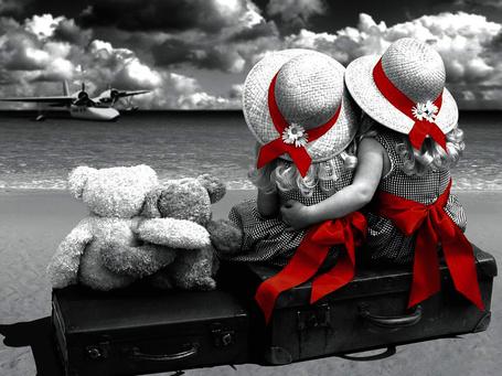 Фото Две девочки сидят обнявшись на чемодане на фоне моря, на которое садится самолет, рядом сидят два плюшевых мишки