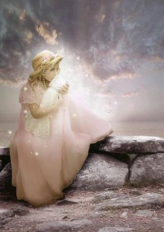 Фото Девочка в белом платье сидит на камнях, держа в руках куклу