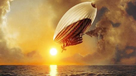 Фото Фантастический дирижабль с трубой, из которой выходит густой, темный дым, летящий над морем на фоне пасмурного неба и ярко светящего солнца