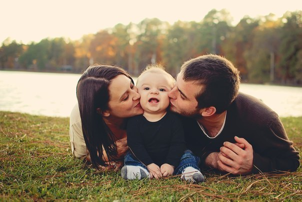 Фото Мужчина с женщиной целуют в щечки своего малыша