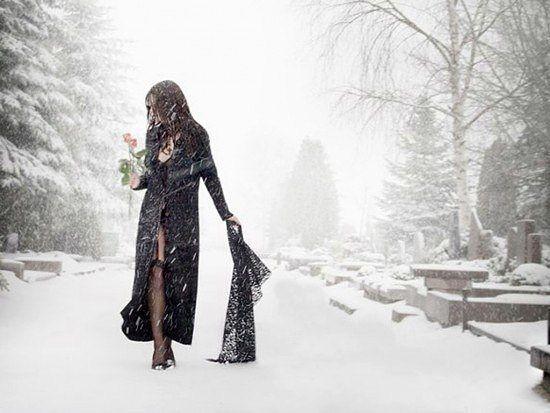 В руке идет по заснеженному кладбищу