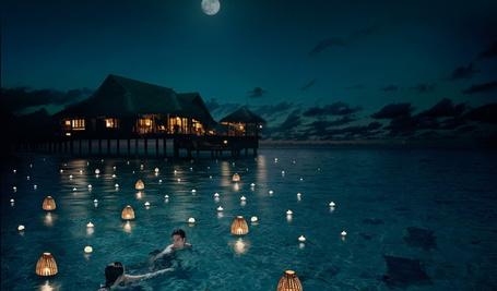 Фото Мужчина и женщина, живущие в бунгало, стоящие на деревянных сваях океанского побережья, плавают в воде среди горящих свечей и фонариков на фоне ночного неба и ярко светящейся луны, Мальдивы / Maldives