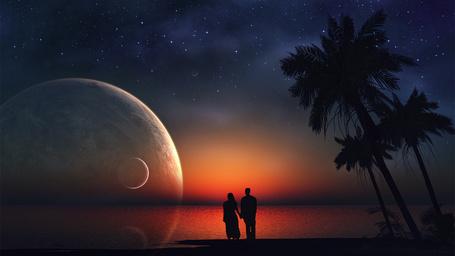 Фото Силуэты мужчины и женщины, стоящих на океанском побережье рядом с растущими пальмами, на фоне звездного ночного неба, багряного заката и взошедших над океаном планет