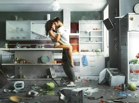 Фото Парень обнимает и целует девушку, сидящую на столе в разгромленной кухне
