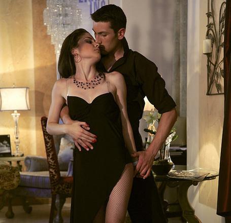 Фото Мужчина обнимает красивую девушку в черном вечернем платье с разрезом