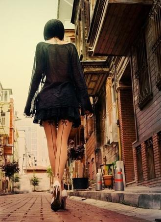 Фото Девушка в черном коротком платье и в белых туфлях на высоком каблуке идет по безлюдной городской улице. Фотограф Метин Демирель / Metin Demiralay