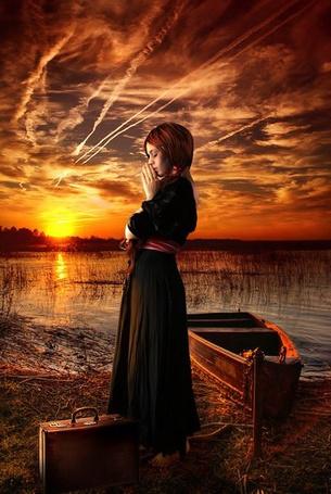 Фото Девушка стоит у реки на фоне заката, рядом стоит чемодан, у берега привязана лодка