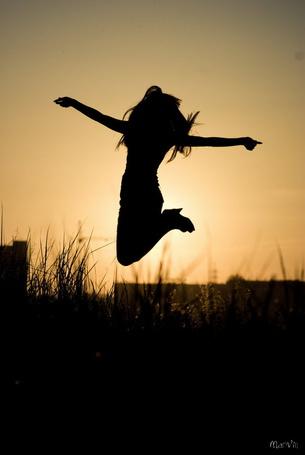 Фото Девушка подпрыгнула в воздухе на фоне закатного неба