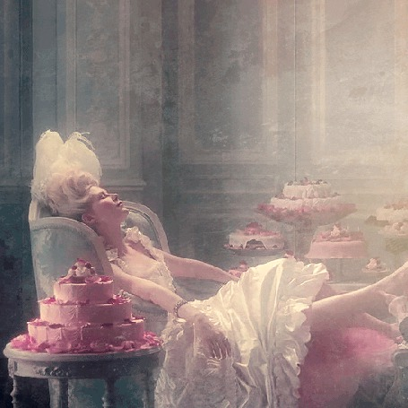 Фото Королева Мария-Антуанетта / Marie Antoinette, чью роль исполняет Кирстен Данст / Kirsten Dunst сидит в кресле, рядом с ней на столе стоит торт, который она попробует, эпизод из фильма Мария-Антуанетта / Marie Antoinette