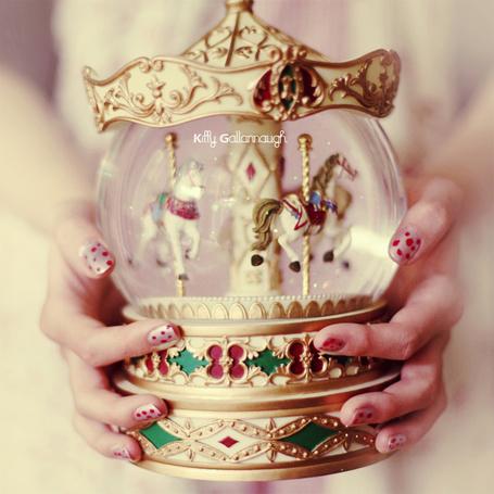 Фото Девочка в руках держит игрушечную карусель