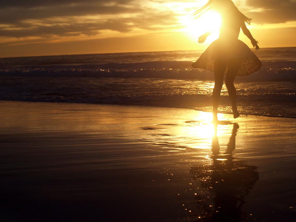 Девушка в летнем платье бежит по берегу моря в лучах закатного солнца
