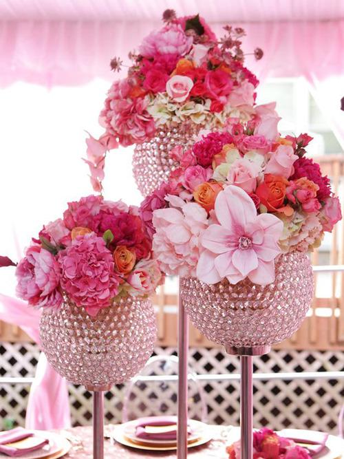 Фото Три больших букета из розовых роз, пионов и гортензии стоят на столе в высоких вазах-подставках
